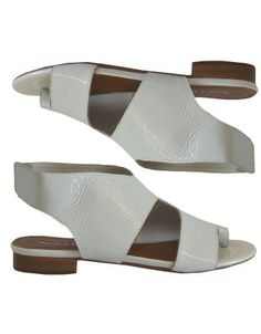 Modern and simple summer footwear from the much-loved label Django & Juliette.  Sleek, easy to wear flat sandals made from lush, soft White Patent Leather.