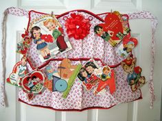 Vintage apron hanging on door with tiny clothespins to hang vintage valentines.