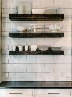 Kitchen with chunky wood floating shelves filled with white pottery over white subway tile