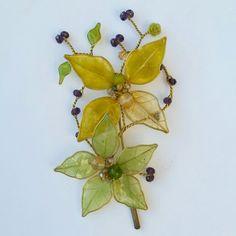 Brooch witn natural skeleton leaves, resin and gemstones..