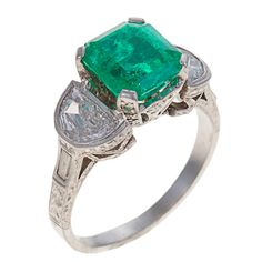 Diamond, Emerald & Platinum Ring. This beautiful ring centers 1 four prong-set emerald-cut emerald, approximately 3.0 carats strong saturation, flanked on either side by 1 bezel-set half-moon shaped diamond, total weight for both approximately 1.20 carats, color: G - H, clarity: VS1 - VS2, the shoulders set with 1 bezel-set baguette-cut diamond and the intricately pierced gallery set with 22 small round diamonds.