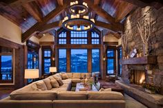 Fireplace Tools as Complementary: Large Sectional Sofa And Throw Pillows In Rustic Living Room Ideas Design With Stacked Stone Wall And Sloped Ceiling Also Fireplace With Fireplace Tools Plus Chandelier And Triangular Window ~ flexform.org Furniture Inspiration