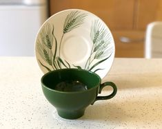This is a fabulous teacup and saucer of Green Wheat Americana Dinnerware by Homer Laughlin. This design began in 1954. The bottom of the saucer is marked: Wheat, Americana, Homer Laughlin, U.S.A. J54N6 1 Tea/Coffee Cup (3 3/4 across and hold 8 oz.)