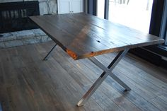 """This table pictured measures 80"""" x 42"""" and comfortably sits 8 adults. This base gives a hat tip to a very traditional design called the sawbuck. It is made from 2"""" steel tubing custom fabricated and powder coated in your choice of flat black, chrome or industrial steel.  The 2"""" thick top is made from locally reclaimed barnwood and can be finished in one of our wide variety of stains or varnishes. Samples available on request. Vist our request a quote page."""