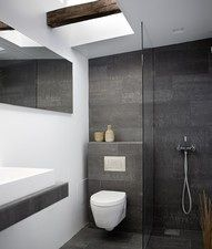 toilet with no floor fitting; false wall used as shelf