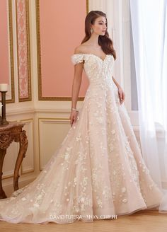 217230 Elnora - Off-the-shoulder tulle and sequin tulle over organza and taffeta full A-line gown features Chantilly lace with Venise lace appliqués, dipped neckline, bodice and skirt adorned with three-dimensional organza flowers, horsehair hemline, chapel length train.