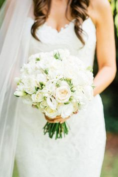 An all-white bouquet was made up of David Austin roses, lisianthus, and freesias | @purcellstudio | Brides.com