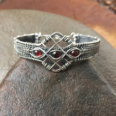 This is a beautifully intricate wire wrap bracelet that I meticulously created for pure beauty with comfort and ease. I started with strong but fluidly movable 16 gauge and 20 gauge sterling silver wire. Magic is woven through this beautiful Garnet bracelet with some finer gauges of