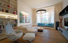 Obývací pokoj s pohodlnou čalouněnou lavicí pod oknem, která doslova láká k lenošení.