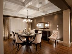 This elegant dining room showcases a neutral and brown color scheme. Cream colored upholstery on the dining chairs looks beautiful against the dark beige walls and hardwood flooring. A dark wooden dining table is complemented with a matching buffet supporting two traditional table lamps. A chandelier hangs from the white, coffered ceiling for a bright addition to the room.