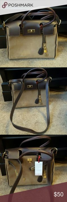 🎉HP🎉 NWT Boutique Beautiful Purse 🎉HP🎉 9/5 NWT Beautiful Boutique Purse with Shoulder Strap Beautiful Suede and Leather in contrasting colors of Beige and Brown. Unique latch closure. Lock and key included. Inside has pocket for a cellphone and also a small zippered pocket. Classic and elegant Boutique Bags Shoulder Bags