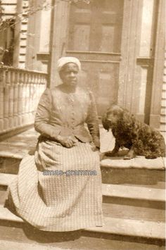 AFRICAN-AMERICAN WOMAN SITTING ON PORCH WITH BLACK COCKER SPANIEL DOG
