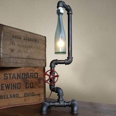 Whether you're a beer nerd, design buff, or both, this Fuse Industrial DIY Pipe Lamp from Peared Creation will tickle your fancy. Its diffuser consists of a pre Pipe Lighting, Rustic Lighting, Vintage Lighting, Lighting Ideas, Lighting Design, Diy Bottle Lamp, Recycled Lamp, Recycled Bottles, Lampe Tube