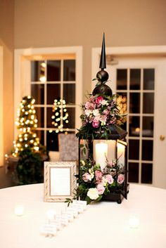 A large lantern overflowing with florals sits atop the welcome ...