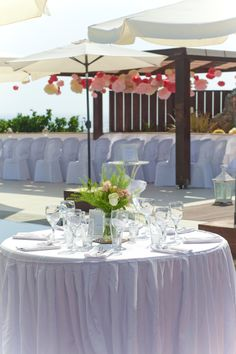 Crisp white crockery and table linen with silver cutlery and crystal glasses www.serenity-weddings.com