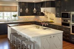 Dark Cabinets - then the island is a different color. Stainless hardware looks cool in here. Then a small tile backsplash of white, tan and gray