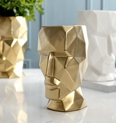 Stylish Geometric Human Face VaseAlmost a work of art in itself, this Stylish Geometric Human Face Vase will finish off your flower or plant arrangement with aplomb.    Its strong, chiselled features are showcased in porcelain white or ceramic gold. Paired together in the same colour or both colours but in differing sizes will make such a visual impact in your home.    These stunning pieces are substantial in size. The smallest size is 19cm wide x 27cm high and the largest standing proud at… Ceramic Plant Pots, Ceramic Vase, Small Succulents, Metal Flowers, Nordic Style, Home Interior, Flower Pots, Bronze, Colours