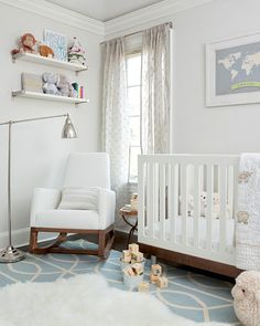 Sweet baby boy& nursery design with pale gray walls paint color, white modern crib, Dwell Studio Gate Azure Cream Rug, white modern glider and white shelves.