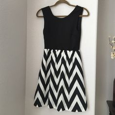 Black and white chevron dress This dress is super cute and hits above the knee. Very flattering throughout. Has an exposed zipper in the back. Dresses