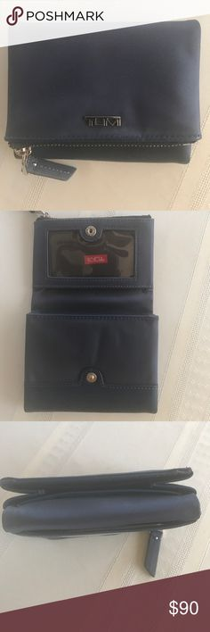 Men's or women's wallet by TUMI This is an elegant wallet for either sex.  Stylish and has plenty of space.  Can hold up to 10 cards.  Zipper pocket for your cash.  Oh and it's backed by the TUMI guarantee. Tumi Bags Wallets