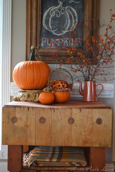 I love the rustic display of pumpkins on this old butcher block type table. I love the old tin coffee pot with Autumn colored twigs. Very country cute!