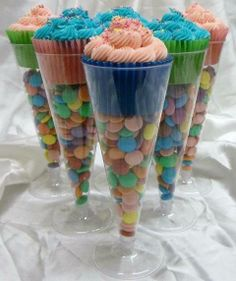 dollar store champagne flutes filled with candy and a cupcake on top!