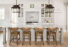 A pair of carriage lanterns illuminate a light gray kitchen island with legs topped with gray and white marble fitted with a farm sink and vintage faucet lined with wood x back counter stools. A cooking alcove is filled with a hidden vent hood over a dark nickel swing arm pot filler lining a marble diamond pattern cooktop backsplash and a stainless steel stove flanked by pull out spice racks.