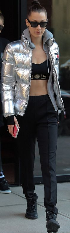 Who made  Bella Hadid's black sneakers, sunglasses, pants, silver down jacket, and crop print top?