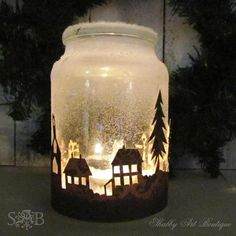 """Illimunate your home with these winter wonderland-style candles. Use a craft knife to cut out the silhouette of some trees and buildings from construction paper. Make sure the total width and height of the cut-outs fit the circumference and height of the your jar. Use glue and Epsom salt to give your candle some """"snow."""" Then wrap the paper silhouette around the jar and secure it with some hot glue. Place a tea candle in the jar for a cute addition to your holiday decor. ..."""