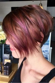 Violet and pink highlights play up this fun red hair color on short hair created by @ardentjourney at @amartesalon. We love the angled bob haircut with messy texture.