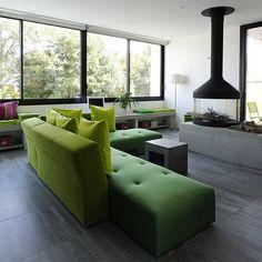 A l'intérieur, le salon organisé autour d'une cheminée centrale décline la gamme des verts, dans un esprit dedans-dehors. Un linéaire de rangement occupe le soubassement des fenêtres.
