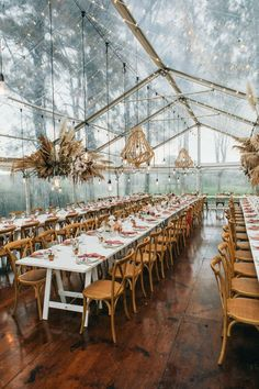 Boho wedding reception of our dreams! Suspended centerpieces with pampas grass, giant chandeliers and our favorite mix of white long tables with wooden crossback chairs