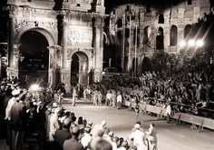 Barefooted runner Abebe Bikila of Ethiopia approaches the Arch of Constantine on his way to winning the Olympic marathon in world-record time of 2:15:16.2. The race was held at night due to sweltering summer heat.