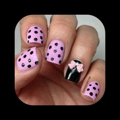Pink nails with black dots and black nail with an pink bow on it.