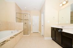 Master suite bathroom with custom tile, separate tub and shower, and dual vanities.  Door at end leads to walk-in closet.