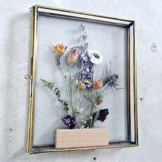 Gedroogde bloemen in gouden display.