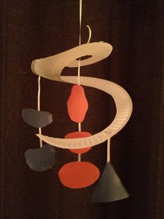 Alexander Calder mobile, made from paper plate, cut in a swirl, white curling ribbon, and construction paper for the shapes, all taped together.