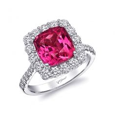 A ravishing platinum ring featuring a 4.41CT cushion cut pink sapphire surrounded by a halo of diamonds.