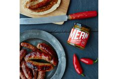 Mean Mustard -  Makers & Merchants. Smooth and sweet with a mean kick of Jalapeño chilli.  A properly British condiment inspired by a classic American-style recipe. This exclusive recipe combines the subtle sweetness and unique spice blend of American mustards with chunky-chopped Jalapeños for an extra bit of bite. It is brilliant with anything smoky and hot off the barbecue, and works wonders with the humble cheese sandwich.