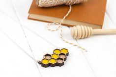 Laser Cut Geometric Honeycomb Necklace.  Ever wanted to explore deep inside a bee nest? This stylish geometric honey comb necklace is awesome for just that!! This combination of hexagon shapes makes up an intricate honeycomb pattern with deep yellow peeping out from the centre.  Laser cut and layered 4mm Cherry wood with dark yellow acrylic/perspex. Comes on a 46cm silver plated necklace chain featuring the Rosebud Casson logo on a 5cm extender.  Matching drop ear rings available here - ...