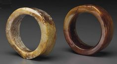 """At Christie's are """"two Jade Bracelets from Southeast China, Neolithic Period (3000 BC): Each a tapering, thick-walled ring, one Liangzhu culture, the stone of yellow and russet-brown color; the other of Liangzhu type, the stone of olive color with opaque areas of brown and ivory color, the outer wall slightly concave, both with satiny polish"""" Sale date: 19 March 2015"""