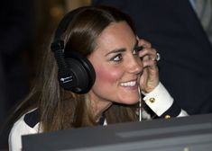 Catherine, Duchess Of Cambridge listens to a morse code message using a replica radio, with event manager Steve Lumby, during a tour the of the restored WWII Codebreaking Huts at Bletchley Park on June 18, 2014