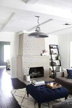 Brick fireplace painted pale grey, white and black rug, and stool