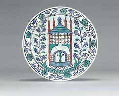 AN IZNIK POTTERY DISH  OTTOMAN TURKEY, CIRCA 1666  With sloping rim and short foot, the white interior painted in cobalt-blue, green, bole-red and black, depicting a central stylized kiosk with pitched roof and four pinnacles, flanked by two hyacinth sprays, the rim with alternating paired blue leaves and green flowerheads, the exterior with alternating blue and green motifs,   11¾in. (29.7cm.) diam.