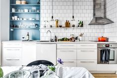 square white subway tile, blue cabinets, open shelves, simple white kitchen