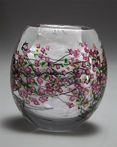 Cherry Blossom Vase by Shawn Messenger. The Cherry Blossom Vase is made with artist created *murrini flowers:Millefiore* and leaves along with black *cane* that represents branches. The background has sparkling gold and silver *dichroic:dichroism* glass along with swirls of white glass chips. The white swirls represent the last bit of snow before the explosion of color comes to life for these beautiful Spring flowering trees. Each piece is unique. Variations in dimensions and floral pattern…