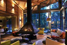 chimenea, salón moderno con toque rústico, chimenea de acero colgante, grandes ventanales y techo con vigas de madera