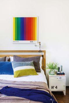 Dormitorio moderno y colorido, con cama de madera y almohadones de terciopelo. La lámina sobre la cabecera se compró en el MoMA.