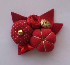 Adorable broche en fleurs de tissus rouges.