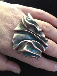 Copper with Turquoise patina and sterling silver band. I imitate draped fabric and ribbon in copper and sterling silver using folding techniques with a hammer and vice. I use an acetylene torch to fabricate the ring (solder it together) before adding the patina. For more scrumptious art
